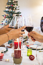 Friends toasting with wine during a Christmas dinner - ABZF001064