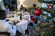 Christmas tree bauble and friends having Christmas dinner - ABZF001073