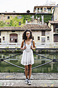 Italy, Milan, portrait of smiling young woman with backpack wearing white summer dress - MRAF000116