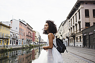 Italy, Milan, young woman with backpack leaning on railing looking at distance - MRAF000119