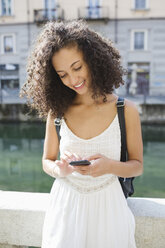 Portrait of smiling young woman text messaging - MRAF000125