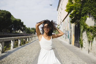 Happy young woman with hands in her hair dancing on the street - MRAF000131