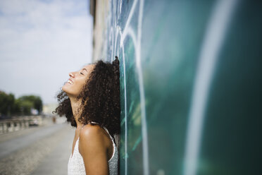 Smiling young woman with eyes closed leaning against wall - MRAF000134