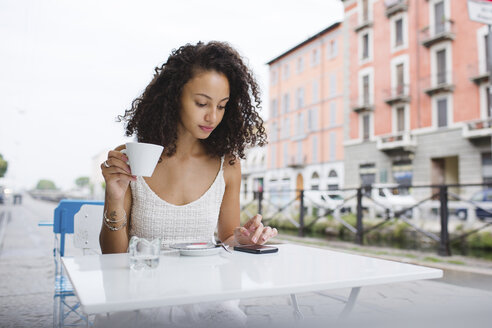Young woman with cup of coffee using her smartphone - MRAF000137