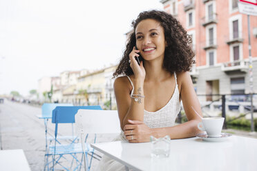 Portrait of smiling young woman on the phone at sidewalk cafe - MRAF000140