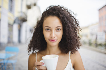 Portrait of young woman drinking coffee at sidewalk cafe - MRAF000143