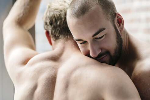 Gay couple embracing at window - MADF001160