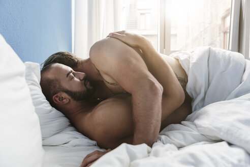 Gay couple embracing in bed - MADF001163
