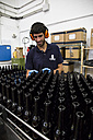 Man working in beer bottling plant - ABZF001080