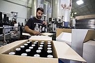 Man working in beer bottling plant - ABZF001089
