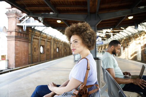 Young woman sitting on bench at train station - FKF002059