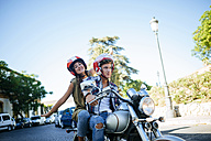 Happy young couple driving on a motorbike - KIJF000731