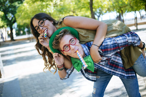 Young couple having fun with party blowers, joke glasses and caps - KIJF000737