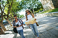 Two young tourists with camera and city map walking around - KIJF000740