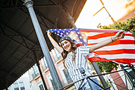 Portrait of smiling young woman posing with American flag - KIJF000767