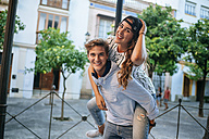 Happy young man giving his girlfriend a piggyback ride - KIJF000770