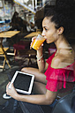 Young woman drinking glass of orange juice in a coffee shop - MRAF000152