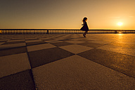 Italy, Livorno, silhouette of little girl dancing on Terrazza Mascagni at evening twilight - OPF000124