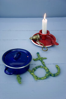 Blue cooking pot on table mat made from wool and wire with burning candle in background - GISF000246