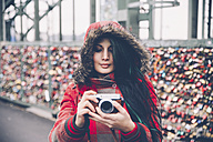 Germany, Cologne, woman with camera at Hohenzollern Bridge - RTBF000283