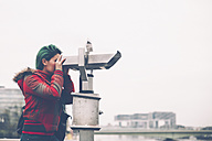 Germany, Cologne, woman looking through coin operated binoculars - RTBF000286