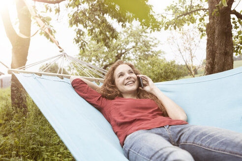 Smiling woman in hammock on cell phone - RBF005076