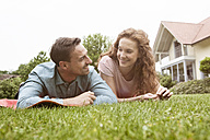 Smiling couple lying on lawn in garden - RBF005079