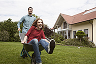 Man pushing happy woman in wheelbarrow in garden - RBF005091