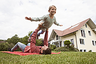 Father playing with daughter in garden - RBF005100