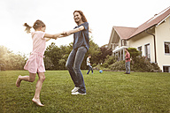 Mother and daughter dancing in garden with family in background - RBF005109