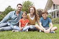 Portrait of smiling family sitting in garden - RBF005124