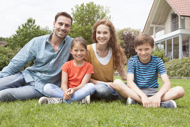 Portrait of smiling family sitting in garden - RBF005124