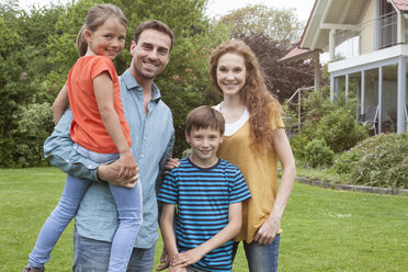 Portrait of smiling family standing in garden - RBF005133