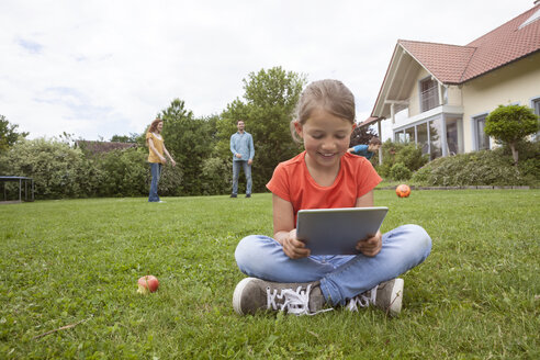 Smiling girl sitting in garden using tablet with family in background - RBF005139
