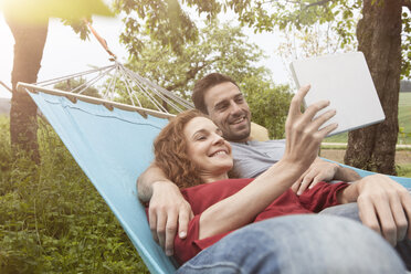 Smiling couple in hammock using tablet - RBF005145