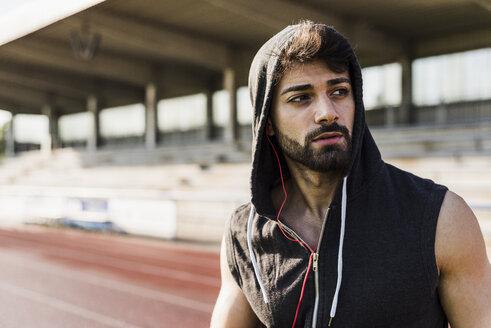 Young man wearing hooded top on tartan track - UUF008277