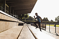 Athlete exercising on grandstand of a track and field stadium - UUF008286