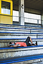 Young man with headphones lying on grandstand - UUF008304