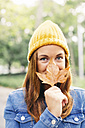 Portrait of smiling young woman wearing yellow cap covering mouth with autumn leaf - EBSF001674