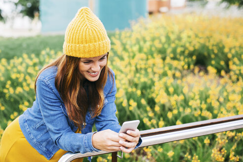 Smiling young woman wearing yellow cap looking at cell phone - EBSF001677