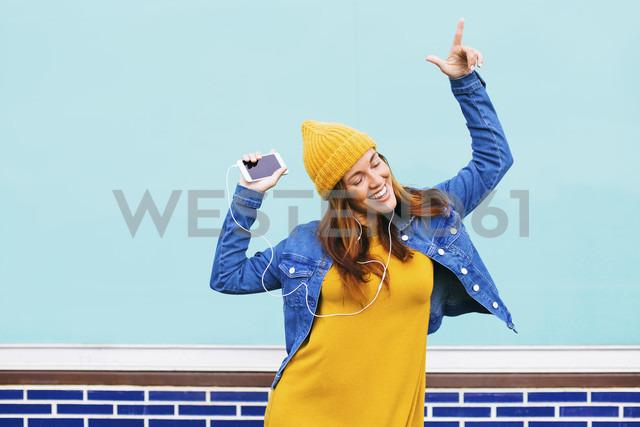 Dancing young woman wearing yellow cap and dress - EBSF001680 - Bonninstudio/Westend61
