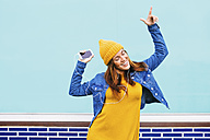 Dancing young woman wearing yellow cap and dress - EBSF001680