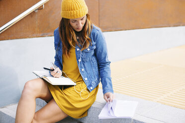 Young woman with notebook sitting on steps - EBSF001689