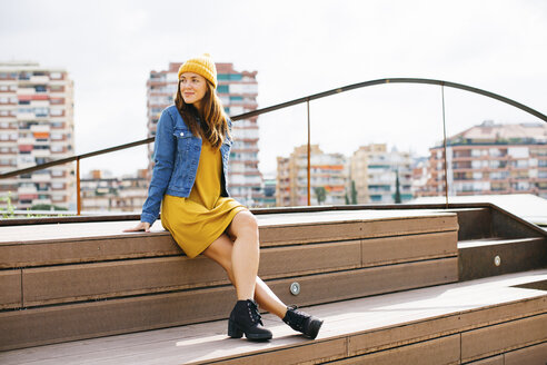 Smiling young woman wearing yellow cap and dress sitting on steps - EBSF001695