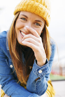 Portrait of laughing young woman wearing yellow cap - EBSF001698