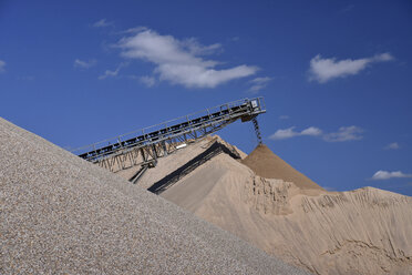 Conveyor belt pouring sand on heap in gravel pit - LYF000568