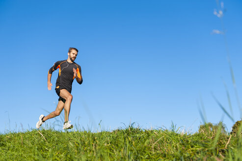 Man running on meadow under blue sky - DIGF001073