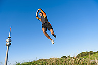 Athlete jumping on meadow under blue sky - DIGF001076