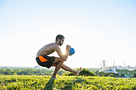 Man exercising with kettlebell on a meadow - DIGF001091