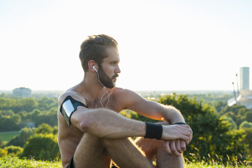 Athlete sitting on a meadow listening to music after workout - DIGF001094